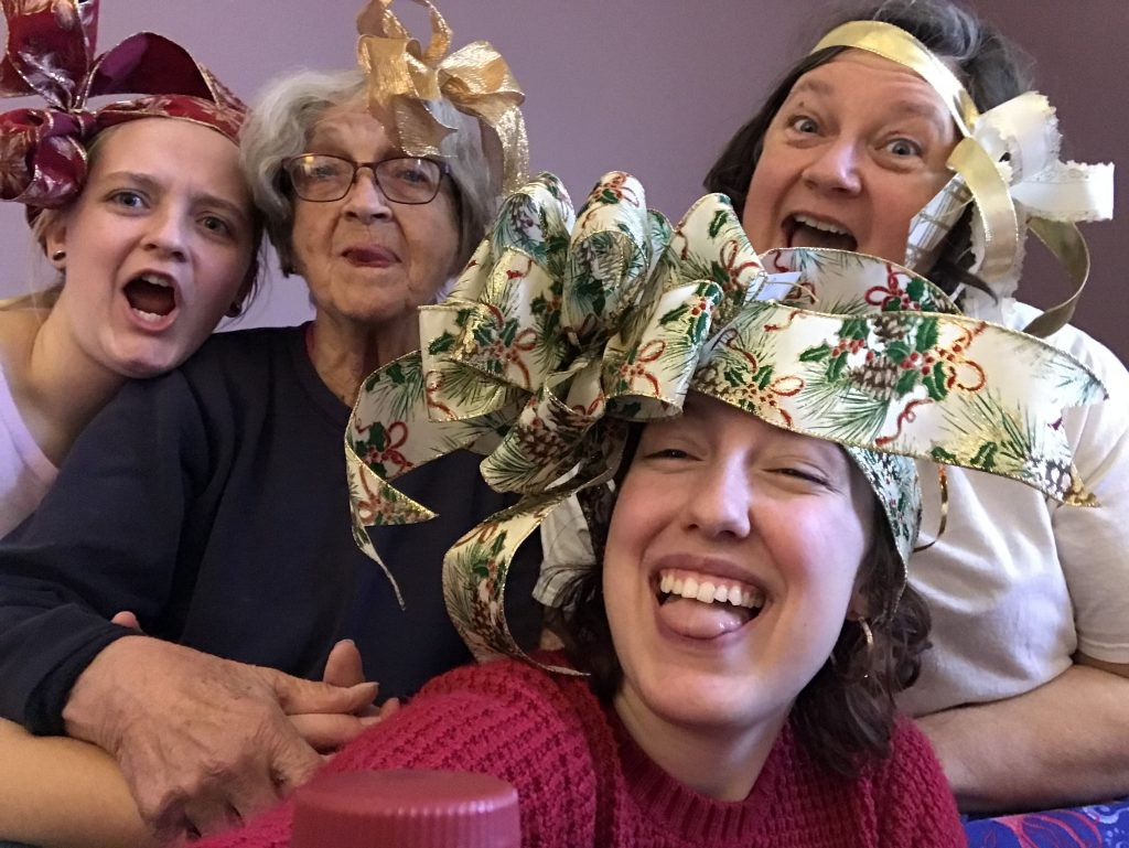 Sister, Grandma, Mom, and Bailey making crazy faces with ribbons on their heads