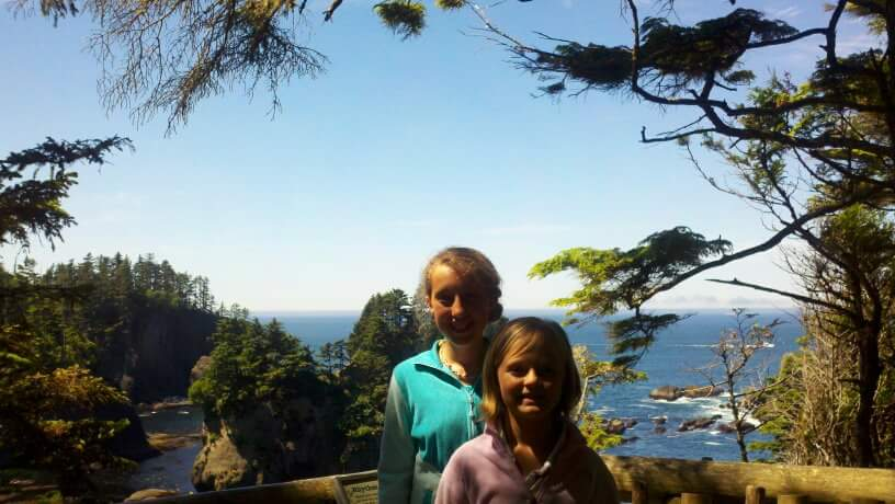 Bailey and sister posing infront of overlook of ocean